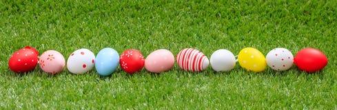 målat gräs för 2 placerade allt för easter för hinkfågelungebegreppet blommor ägg barn Färgrika ägg på grönt gräs, baner, kopieri Arkivbild