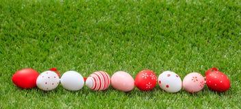 målat gräs för 2 placerade allt för easter för hinkfågelungebegreppet blommor ägg barn Färgrika ägg på grönt gräs, baner, kopieri Arkivfoto