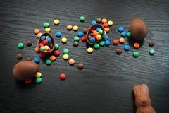 Målat påskbegrepp och chokladägg, sötsaker, droppar, candys Arkivfoto