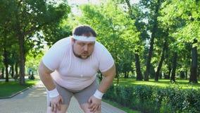 Målmedveten fet manspring parkerar in, ut ur andedräkt, ihärdig motivation lager videofilmer