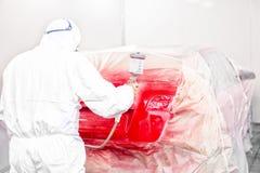 Målning för auto mekaniker med retuschsprutan en röd bil i specialt bås arkivbild