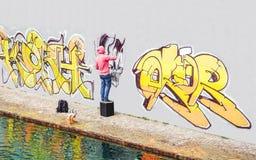 Målning för gatagrafittikonstnären med en färgsprej kan en grafitti på väggen i staden - begrepp av samtida konstlivsstilen royaltyfria foton