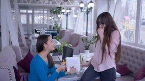 Målplanet, flickan med anteckningsboken och pennan i hand skriver sunda grönsaker bantar ner samman med flickvän under lunch stock video