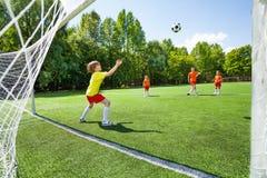 Målvakten försöker att fånga fotbollen som flyger upp Arkivfoton