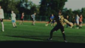 Målvakten sparar en boll, och kastet in till en grad under fotbollleken, fotbollsspelare anfaller, suddigt för bakgrund arkivfilmer