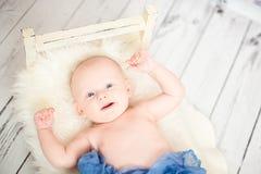 2 månad behandla som ett barn att le som täckas med den blåa textilen Arkivbilder