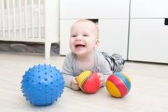 6 månad lyckligt behandla som ett barn le som är gulligt, flickalekbollar Royaltyfri Foto