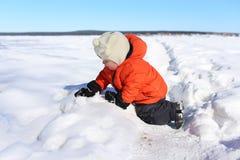 18 månader behandla som ett barn att spela med snö Arkivbilder