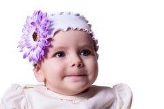 6 månader behandla som ett barn flickan med en blomma på hennes huvud som ler på en vit Arkivfoton