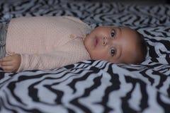 4 månader gammal sötsak behandla som ett barn flickan på säng med härliga ögon royaltyfria foton