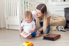 10 månader gammalt litet barnpojkesammanträde på golv med modern och sebilder in i bok Royaltyfri Foto