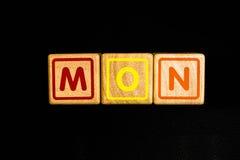 måndag på wood kubik på svart bakgrund royaltyfria foton