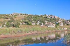 Måne över den steniga kullen Fotografering för Bildbyråer