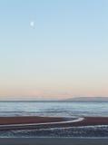 Måne över firthen av Clyde, från den Prestwick stranden, Skottland Arkivbild