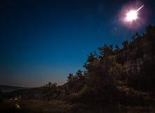 Måne bak träd i natthimmel i zaragoza Arkivbilder