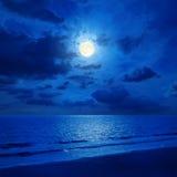 Måne i molnig himmel och hav med reflexioner Royaltyfri Foto