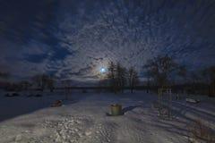 Måne- och cirrusmolnmoln över by royaltyfria bilder