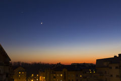 Måne och stjärna i aftonen över godshus som sovande faller i staden Arkivbild