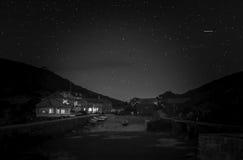 Måne- och stjärnaslingor över havet arkivfoto