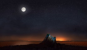 Måne och stjärnor över stenen i öken Royaltyfria Bilder