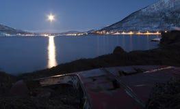 Måne som skiner på det skeppsbrutna fartyget på den arktiska kustlinjen Arkivfoton