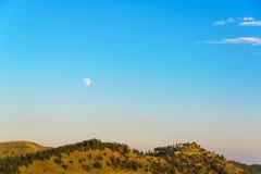 Måne som stiger över kullar fotografering för bildbyråer