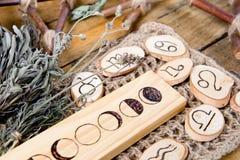 Månefaser och astrologiska symboler med örtpackar på lantlig träbakgrund royaltyfria bilder