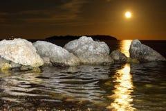 Månelöneförhöjningen som reflekterar på vattnet med, vaggar och ön royaltyfri bild