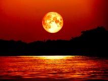 Månen och månsken för fullt blod på floden, beståndsdelar av denna avbildar f royaltyfri foto