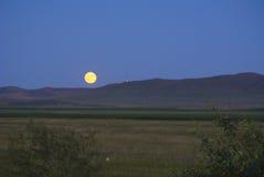 Månen stiger upp på i den Inner Mongolia grässlätten Royaltyfria Foton