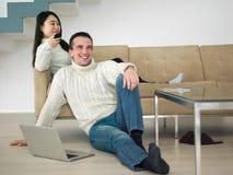 Mång- etniska par på den hållande ögonen på televisionen för soffa royaltyfri bild