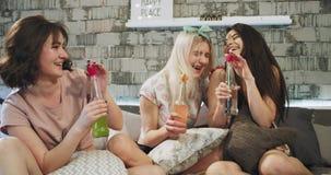 Mång- etniska tonåringdamer på ett modernt vindsovrum, har en sleepovernatt som dricker några färgrika drinkar från stock video