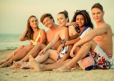 Mång- etniska vänner på en strand Arkivbild