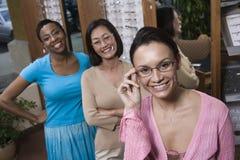 Mång- etniska vänner som försöker på exponeringsglas på optometrikern royaltyfria foton