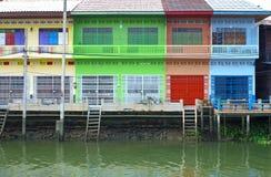 Mång- färga thailändskt utformar hus bredvid kanalen Arkivbilder