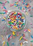 Mång--färgad bakelsegarnering i en glass krus Arkivbild