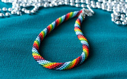 Mång--färgad halsband på en textilbakgrund arkivbilder