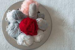 Mång--färgad tråd för att sticka i en maträtt Garn för att sticka på en vit bakgrund Sticka som en sort av handarbete royaltyfri fotografi