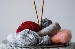 Mång--färgad tråd för att sticka i en maträtt Garn för att sticka på en vit bakgrund Sticka som en sort av handarbete royaltyfria foton