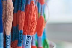 Mång--färgad ull dragar floss i skeins på ställningen i lagret, selektiv fokus arkivfoton