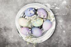 Mång--färgade ägg för påsk i marmorplatta med vita färger Arkivbilder