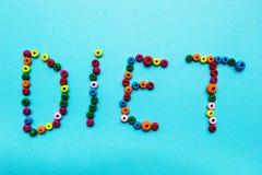 Mång--färgade barns pärlor, spridda på en blå bakgrund Ordet royaltyfri foto
