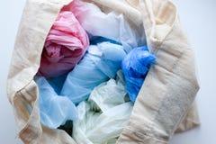 Mång--färgade blåa, röda vita plastpåsar i en trasabomullspåse arkivfoto