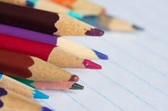 Mång--färgade blyertspennor på denbok sidan Arkivfoton