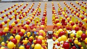Mång--färgade bollar sträcks på rep för garnering som svänger i ljuset lager videofilmer