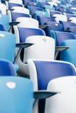 Mång--färgade fåtöljer med nummer på en fotbollsarena Blått- och vitfärg Royaltyfri Foto