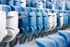 Mång--färgade fåtöljer med nummer på en fotbollsarena Blått- och vitfärg Arkivbilder