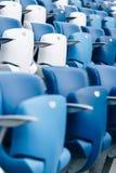 Mång--färgade fåtöljer med nummer på en fotbollsarena Blått- och vitfärg Arkivfoto