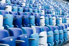 Mång--färgade fåtöljer med nummer på en fotbollsarena Blått- och vitfärg Fotografering för Bildbyråer