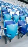Mång--färgade fåtöljer med nummer på en fotbollsarena Blått- och vitfärg Arkivfoton